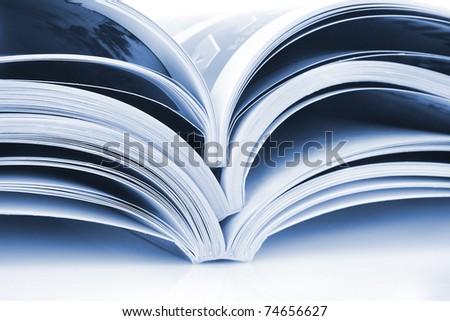 Pile of open magazines isolated on white background - stock photo