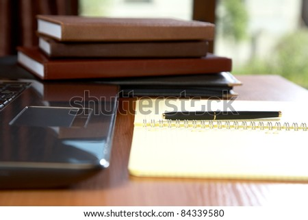 Pile of organizers the laptop writing-book and  pen on a desk - stock photo