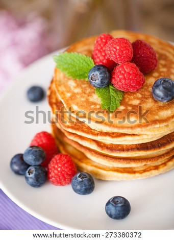 Pile of pancakes with fresh berries on white plate - stock photo