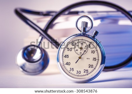 Pile of paper cards, stethoscope and stopwatch - stock photo
