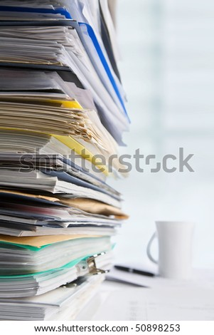 Pile of paperwork with cup and pen on background