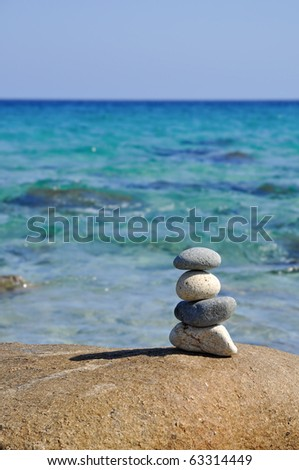 Pile of pebble stones over blue sky and sea. Sardinia. Italy.