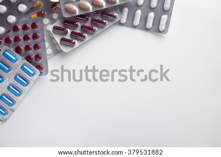 Pile of pills in blister packs on a white table background. Horizontal composition. Top view