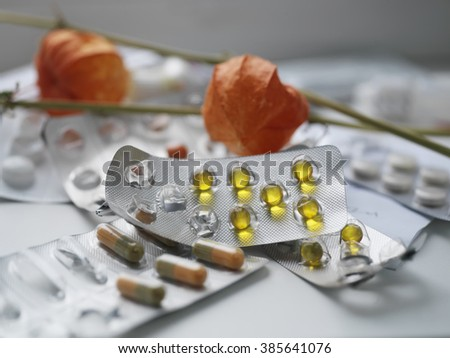 Pile of pills laid in mess on a table, red flower in the blurred background, selective focus closeup shot - stock photo