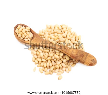 Pile of pine nuts with the wooden spoon over it, composition isolated over the white background