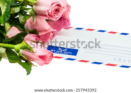 Pile of pink rose blossoms with White Vintage Envelope on white background - stock photo