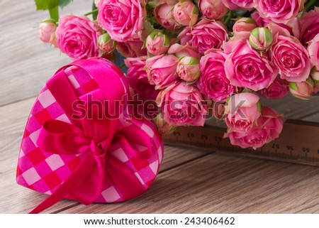 pile  of  pink small fresh  roses and heart box  on wooden background - stock photo
