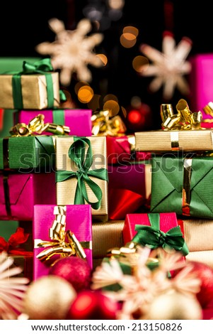 Pile of plain Christmas presents between blurred baubles and straw stars. Vibrant colors. Magenta, gold, green and red. Tightly framed. Narrow depth of field. Bokeh over pitch black background. - stock photo