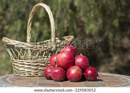 Pile of pomegranates with natural basket against blurred outdoor background