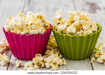 Pile of popcorn in colorful bowls on wooden white background  - stock photo