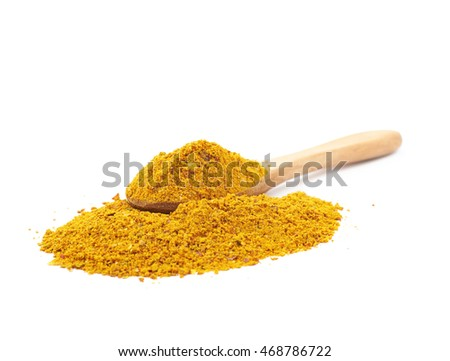 Pile of powdered yellow curry spice with a wooden spoon over it, composition isolated over the white background