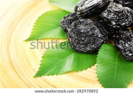 Pile of prunes with leaves on wooden tray, closeup - stock photo