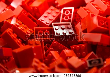 Pile of red color building blocks with selective focus and highlight on one particular block using available light. - stock photo