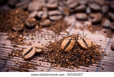 Pile of roasted coffee beans and granules on bamboo mat surface - stock photo