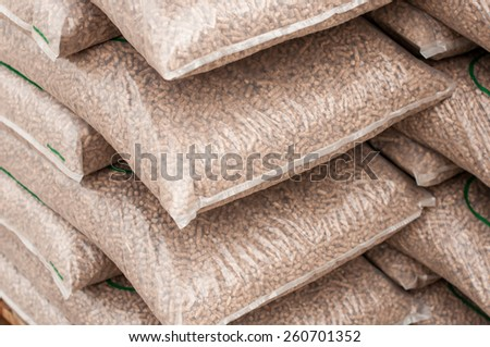 Pile of sacks of pellets, which are stacked on pallets - stock photo
