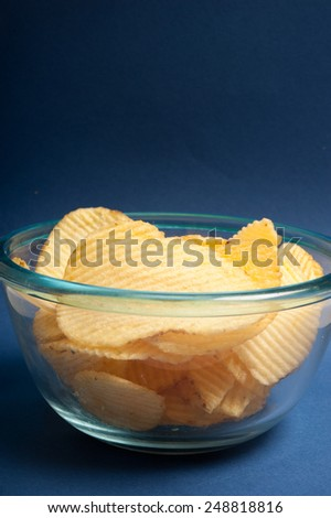 pile of salty chips in glass bowl over blue background with copy space  - stock photo