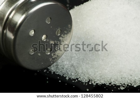 Pile of spilled salt and saltshaker black isolated - stock photo