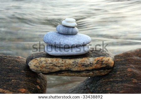 pile of stones on two rocks, the sea in the background - stock photo