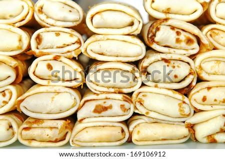 Pile of stuffed pancake rolls, side view - stock photo