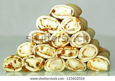 Pile of stuffed pancakes' roll making pyramid - stock photo