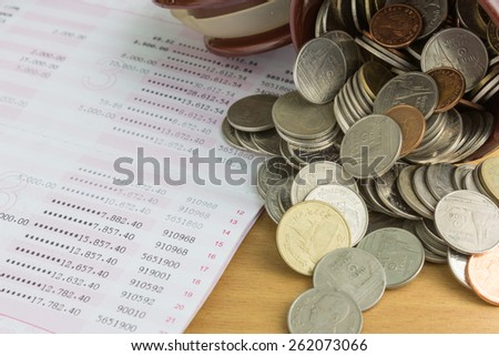 pile of Thai coins and passbook