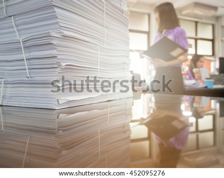 Pile of unfinished documents on office desk with businesswoman background - stock photo
