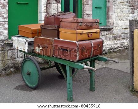 Pile of vintage luggage on railway porters trolly - stock photo