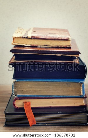pile of vintage old books stacked on table - stock photo