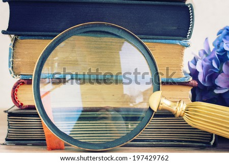 pile of vintage old books stacked on table with looking glass - stock photo