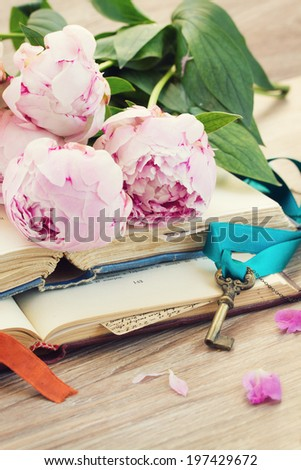 pile of vintage old books with peony flowers stacked on table - stock photo
