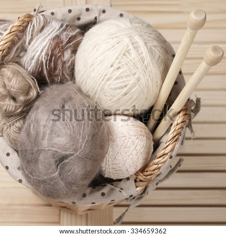Pile of warm woolen yarn and wood needles in rustic wicker basket on wooden table. Top view point. - stock photo