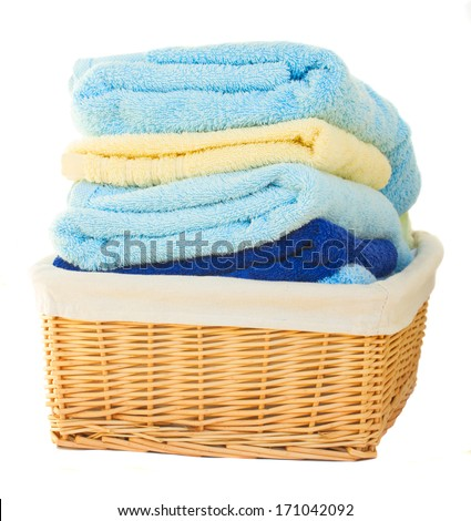 Pile of washed towel in basket  isolated on white background - stock photo