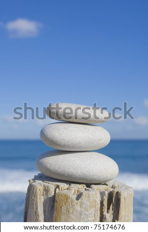 Pile of white pebbles on an old wooden post in front of the sea. - stock photo