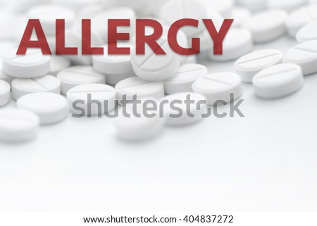 Pile of white pills in closeup on white background with text ALLERGY. Bright light
