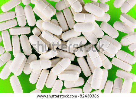 Pile of white pills on green plate - stock photo