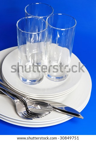 Pile of white plates, glasses with forks and spoons on silk napkin. Blue background - stock photo