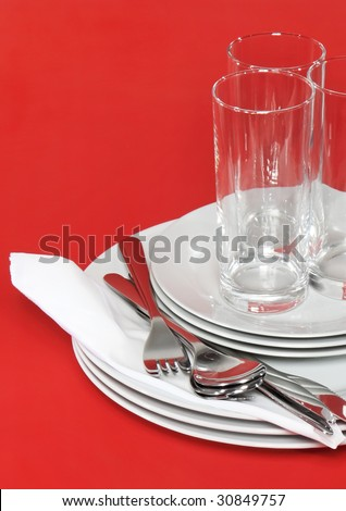 Pile of white plates, glasses with forks and spoons on silk napkin. Red background - stock photo