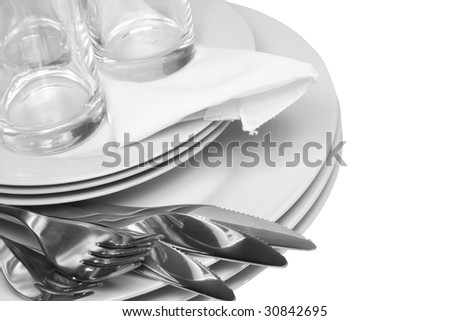 Pile of white plates, glasses with forks and spoons,silk napkin. Isolated - stock photo