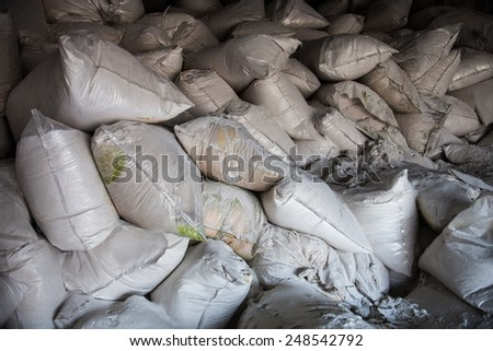 Pile of white sacks with synthetic fertilizer. - stock photo