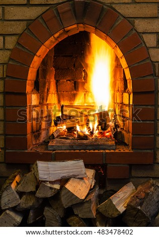 pile of wood and logs burning in indoor brick fireplace in country cottage