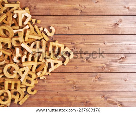 Pile of wooden letters over the surface of the brown wooden boards - stock photo