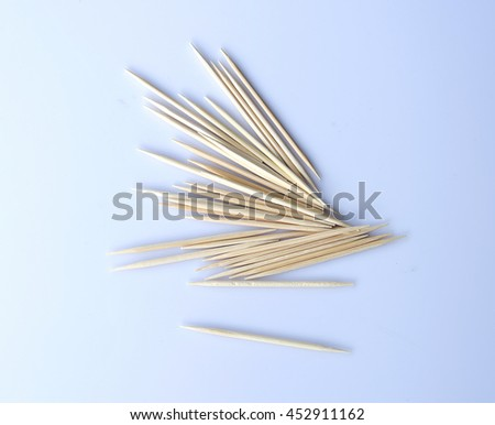 Pile of wooden toothpicks made from bamboo on white background. Selective focus.