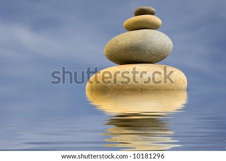 pile of zen round stones with blue sky and water reflexion - stock photo