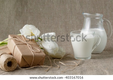 pile parcel wrapped with brown kraft paper. Glass of milk - stock photo