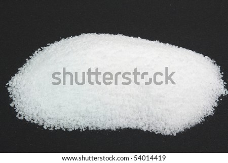 Pile Pickling Salt over black. Picture of Pile Pickling Salt, which is fine grain not iodine sea salt  on black background used for Pickling of Food. - stock photo