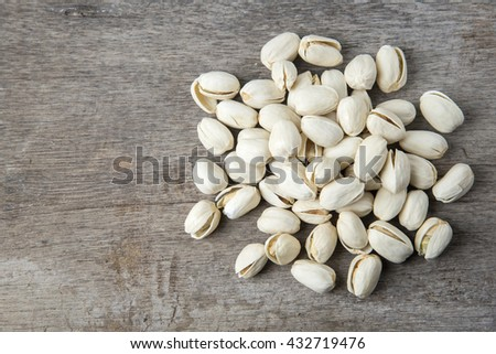 pile pistachios on a wooden table,Selective focus. - stock photo