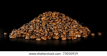 Pile, roasted, dark, smelling of coffee, on a black background. - stock photo