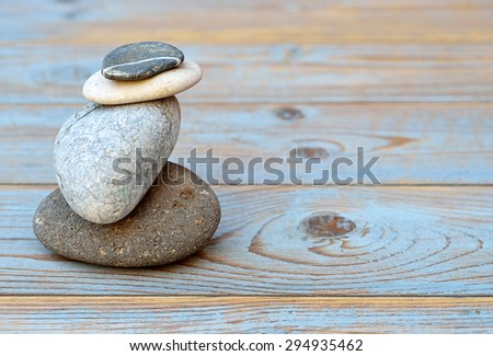 Pile up   grey cairn zen stones on empty blue grey wooden background  - stock photo