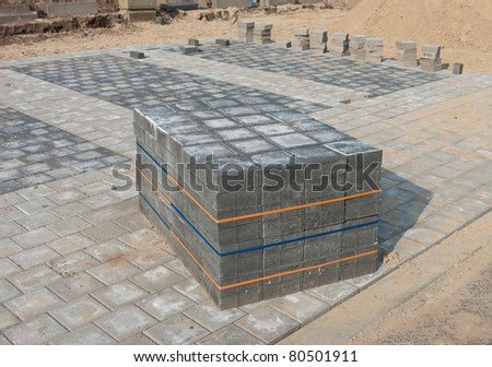 piled up bricks on a newly paved parking area