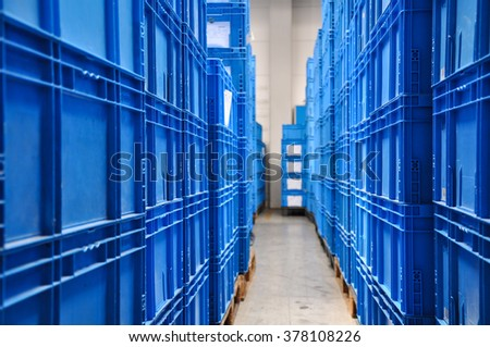 Piles of blue plastic containers in a warehouse in Germany. The boxes are used in the logistics chain transporting the produced goods.Selective focus on the front of the photo.